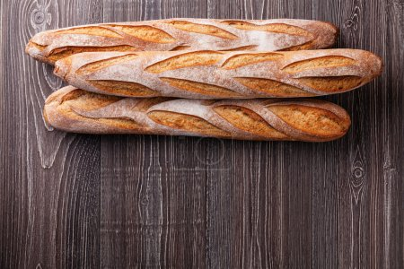 Photo for Three fresh French Baguettes on gray wooden background, top view - Royalty Free Image