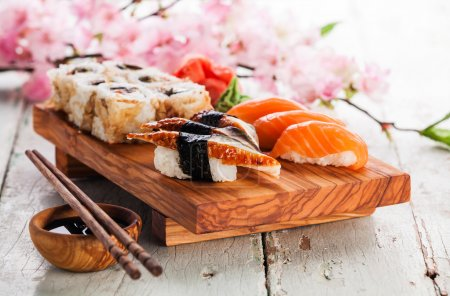 Photo for Sushi Set with sashimi and sushi rolls on olive wood board on white wooden background, close up - Royalty Free Image