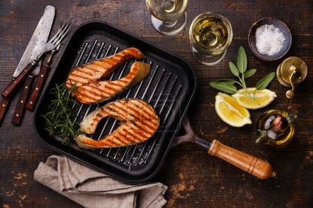 Photo pour Steaks de saumon grillé sur une poêle à griller avec du vin sur fond bois, vue sur le dessus - image libre de droit