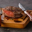 Filet Mignon Steak on wooden board on black backgr...