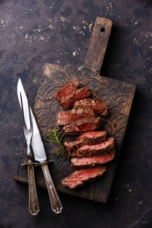 Photo for Sliced grilled Beef steak with knife and fork for meat on wooden cutting board - Royalty Free Image