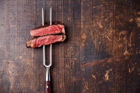Photo pour Tranches de steak grillé moyen rare Ribeye sur fourchette à viande sur fond de bois foncé - image libre de droit