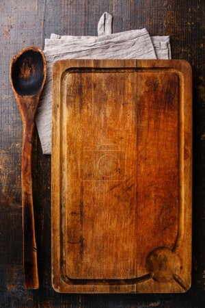 Photo for Chopping board and old wooden spoon kitchenware on dark wooden background - Royalty Free Image