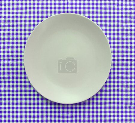 der Teller auf karierter Tischdecke