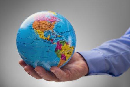 Photo pour Homme d'affaires, tenant le monde dans le creux de son concept de mains pour les entreprises mondiales - image libre de droit