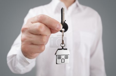 Photo for Man holding out house key on a house shaped keychain - Royalty Free Image