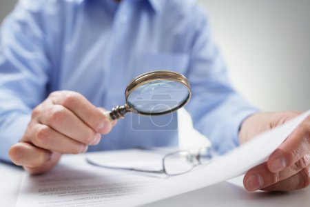 Businessman reading documents with magnifying glas...