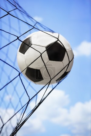 Photo for Soccer ball in back of the net concept for goal, scoring, winning and team competition - Royalty Free Image