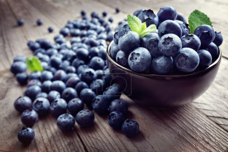 Photo for Blueberries antioxidant organic superfood in a bowl on a rustic table concept for healthy eating and nutrition - Royalty Free Image