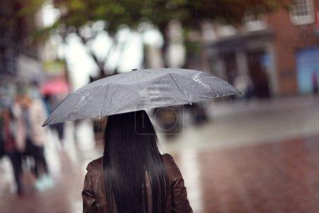Photo pour Des gouttes de pluie tombent sur une femme tenant un parapluie noir dans un concept de rue commerçante pour le mauvais temps, l'hiver ou la protection - image libre de droit