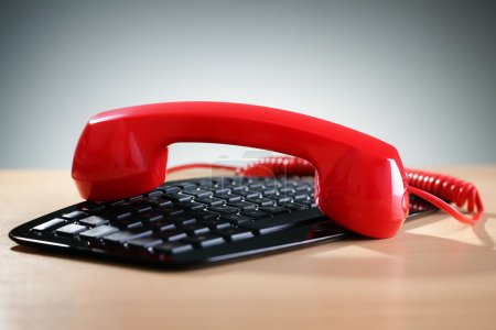 Red telephone receiver on keyboard