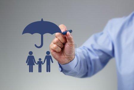 Photo pour Main d'homme d'affaires un parapluie au-dessus d'un concept de famille pour la protection, de sécurité, de finance et d'assurance de dessin - image libre de droit
