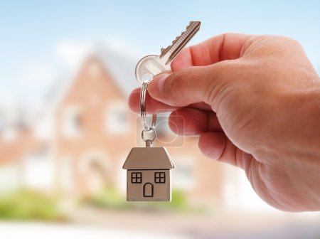 Photo for Holding house keys on house shaped keychain in front of a new home - Royalty Free Image