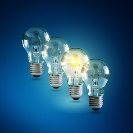 Photo pour Ampoule éclairée dans une rangée de dim ceux concept pour la créativité, l'innovation et solution - image libre de droit