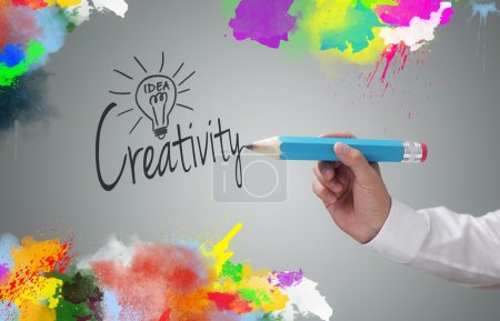 Photo for Businessman writing the word creativity and painting abstract colorful design on gray background concept for business idea, imagination and inspiration - Royalty Free Image