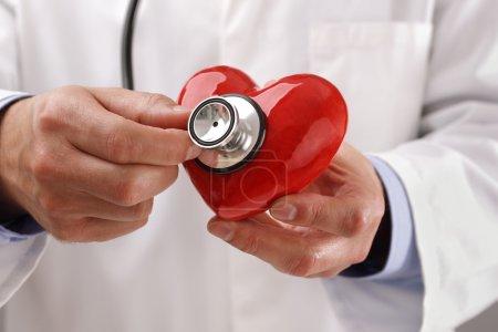 Photo pour Médecin ou cardiologue tenant le cœur à l'écoute du concept de pouls pour les soins de santé et le diagnostic pouls cardiaque médical test - image libre de droit