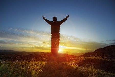 Photo pour Silhouette d'un homme avec les mains levées dans le concept du coucher du soleil pour la religion, de culte, de prière et de louange - image libre de droit