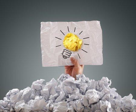 Photo pour Homme d'affaires enterré sous une pile de papiers froissés avec un signe d'idée - image libre de droit
