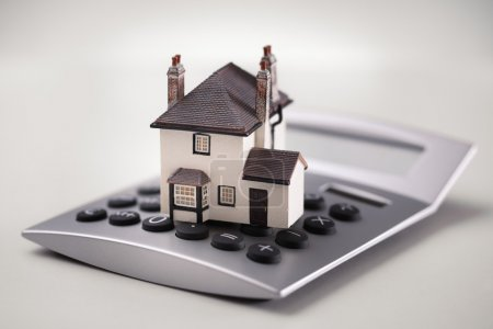 House resting on calculator