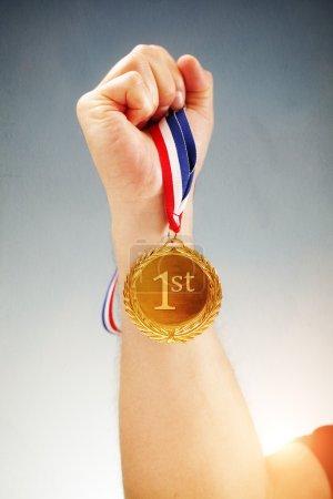 Photo pour Gagner la première place main tenant la médaille d'or - image libre de droit