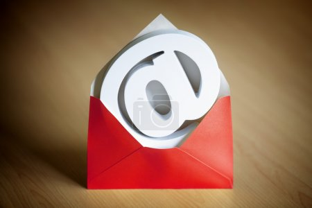 Photo for E-mail symbol inside a red envelope on a desk - Royalty Free Image
