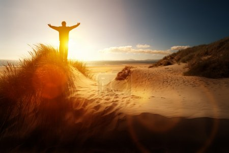 Photo for Silhouette of a man with hands raised in the sunset on a beach concept for religion, worship, prayer and praise - Royalty Free Image