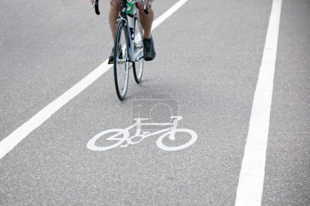 Photo for Commuter riding a bicycle on a city cycle lane or path across white painted bike symbol - Royalty Free Image