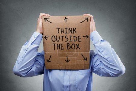 Foto de Hombre de negocios con caja de cartón en la cabeza con texto pensar fuera el concepto de caja para lluvia de ideas, creatividad, innovación, estrategia o individualidad - Imagen libre de derechos