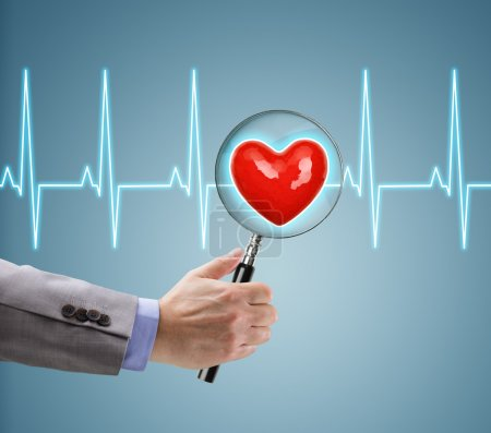 doctor with magnifying glass on heart