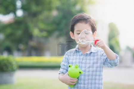 Cute asian child is blowing a soap bubbles outdoor...