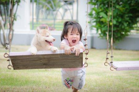 Foto de Bebé asiático en columpio con cachorro husky siberiano - Imagen libre de derechos