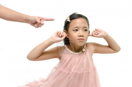 Photo for Little asian girl covering ears while mother scolding - Royalty Free Image