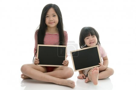 Little asian boy and girl sitting and holding  chalkboard