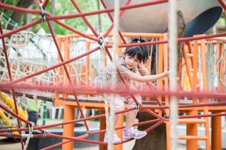 Foto de Pequeña chica asiática se divierte en parque de aventuras - Imagen libre de derechos
