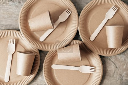 Photo for Wooden forks and paper cups with plates on wooden background. Eco friendly disposable tableware. Also used in fast food, restaurants, takeaways, picnics. Top view. Copy, empty space for text. - Royalty Free Image