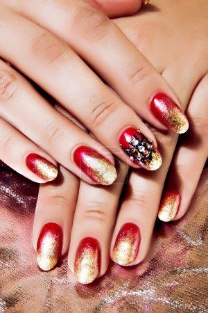 Photo pour Gros plan des mains féminines portant brillant vernis rouge et or sur ongles - image libre de droit