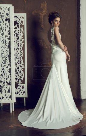 Foto de Hermosa joven novia en vestido con clase, posando en el interior - Imagen libre de derechos