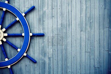 Photo pour Ancienne roue de barre en bois bleu vintage sur le mur - image libre de droit