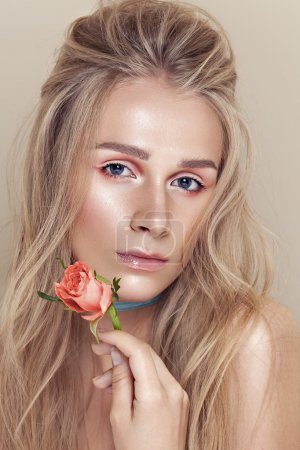 Portrait of young beautiful woman with stylish make-up and rose