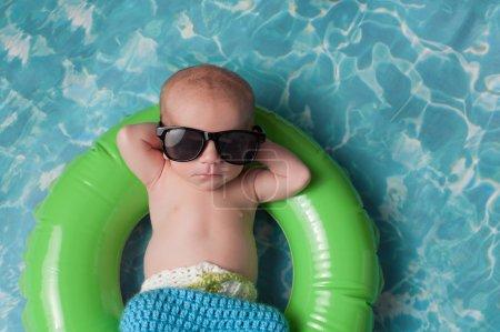 Photo pour Quatre semaine bébé nouveau-né garçon dormant sur un anneau de minuscules bain gonflable. Il est vêtu de bonneterie board shorts et lunettes de soleil noirs. - image libre de droit