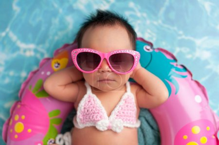 Photo for Nine day old newborn baby girl wearing pink sunglasses and a pink and white bikini. She is sleeping on a tiny inflatable swim ring. - Royalty Free Image
