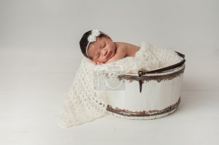 Newborn Girl Sleeping in Wooden Bucket