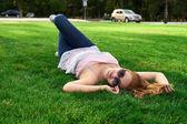 šťastná žena s brýlemi, ležící na trávě