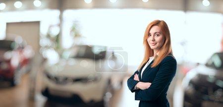 Photo pour Consultant de la jeune femme dans la salle d'exposition est debout près de voiture. - image libre de droit