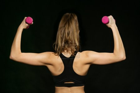 back of athletic woman doing sport, lifting weights