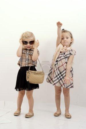 Photo pour Les photos représentent des enfants, deux petites filles mignonnes montrant de beaux vêtements, kids fashion. - image libre de droit