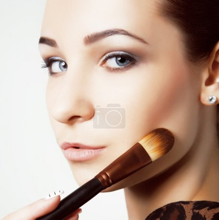 Beauty young Girl with Makeup Brushes. Natural Make-up for Brunette Woman with bleu Eyes. Beautiful Face. Makeover. Perfect Skin. Applying Makeup