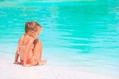 Rozkošná holčička na pláži během letních prázdnin