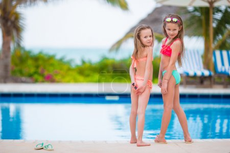 Photo for Adorable little girls playing in outdoor swimming pool - Royalty Free Image