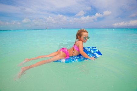 Little cute girl surfing in the turquoise sea